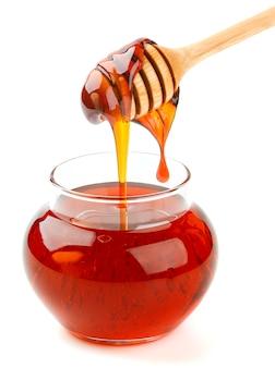 Pot de verre et bâtonnet de miel isolé sur blanc, miel verser