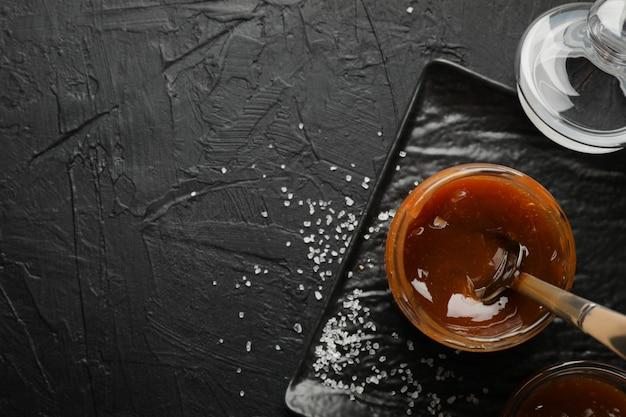 Pot en verre avec caramel salé et cuillère sur l'espace noir, copie espace