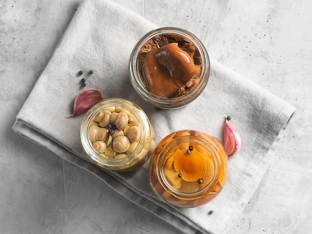 Pot en verre avec des champignons en conserve avec de l'ail et du poivre.