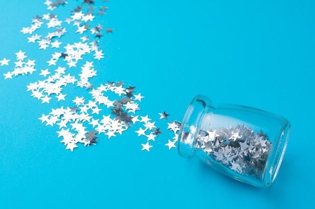 Pot en verre avec des confettis dispersés sur bleu