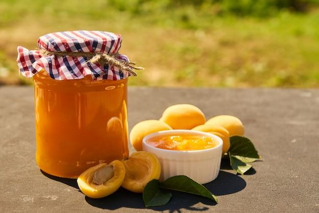 Pot en verre avec de la confiture d'abricot bio maison et des abricots mûrs sur fond noir. style rustique, mise au point sélective