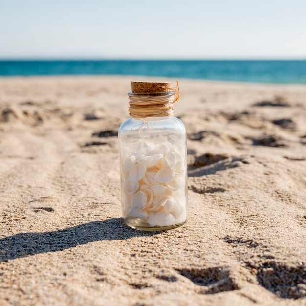 Pot de verre avec des coquilles sur le sable