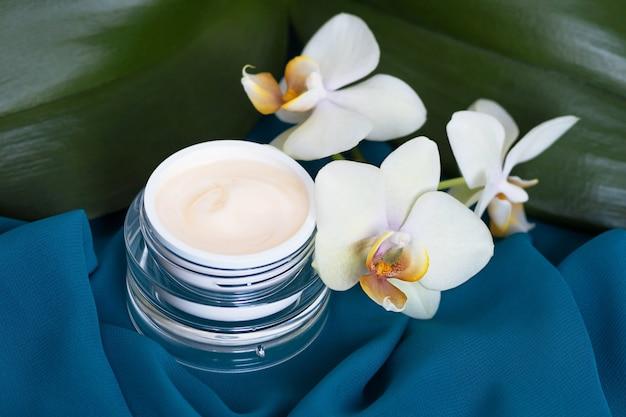 Pot en verre avec crème hydratante et liftante et fleurs d'orchidées phalaenopsis blanches