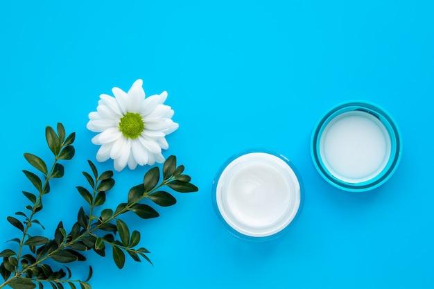 Pot en verre de crème, pommade à la marguerite naturelle. cosmétiques à base de plantes, concept de soins de la peau. bouteille avec lotion et fleur de camomille blanche, branche verte sur fond bleu.