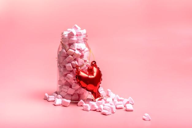 Pot en verre avec de délicieux bonbons en forme de coeur