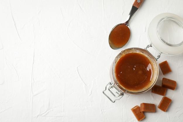 Pot en verre avec du caramel salé et des bonbons sur un espace blanc, copiez l'espace