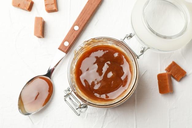 Pot en verre avec du caramel salé et des bonbons sur un espace blanc, vue de dessus