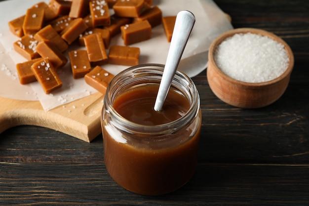 Pot en verre avec du caramel salé et des bonbons sur un espace en bois, close up