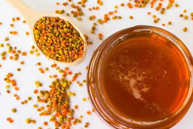Pot en verre avec du miel et du pollen dans une cuillère en bois sur un espace blanc.
