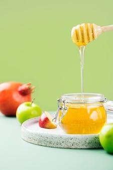 Pot en verre avec du miel frais, une cuillère de miel, de la pomme et de la grenade sur fond vert clair. concept créatif nouvel an juif joyeuses fêtes roch hachana. disposition des symboles traditionnels.vue d'en haut