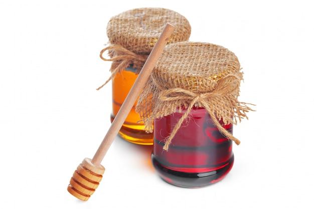 Pot en verre avec du miel sucré isolé sur blanc