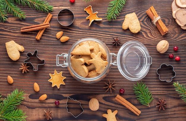 Pot en verre avec du pain d'épice parmi les noix et emporte-pièces et branches de sapin sur table en bois brun