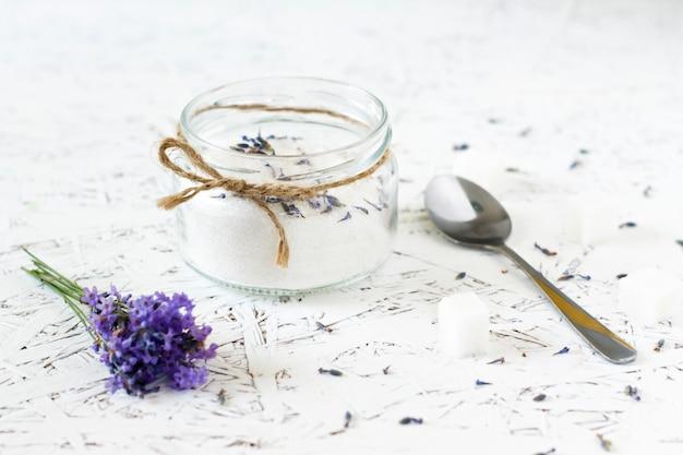 Pot en verre avec du sucre de lavande, de la lavande fraîche sur un fond en bois clair
