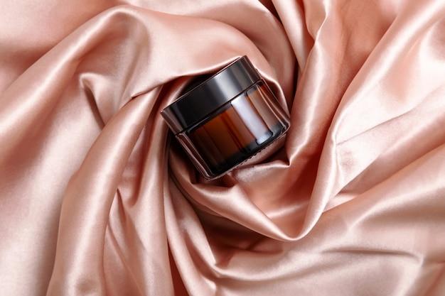 Pot en verre foncé de crème hydratante dans des plis de tissu rose en soie
