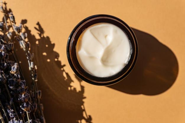Pot en verre foncé avec crème de lavande, fleurs de lavande violette séchée sur fond beige. aromathérapie à base de plantes et soins de la peau.