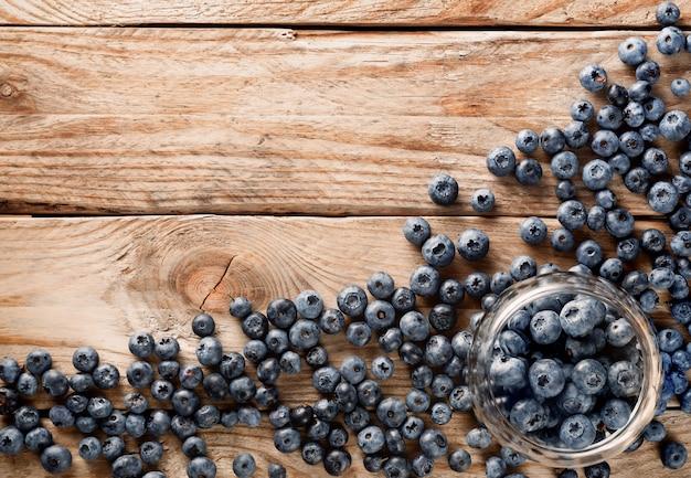 Pot en verre avec des fraises avec des baies éparpillées à proximité sur une vieille table rustique en bois.