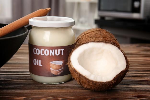 Pot en verre avec de l'huile de noix de coco et des noix sur la table de la cuisine