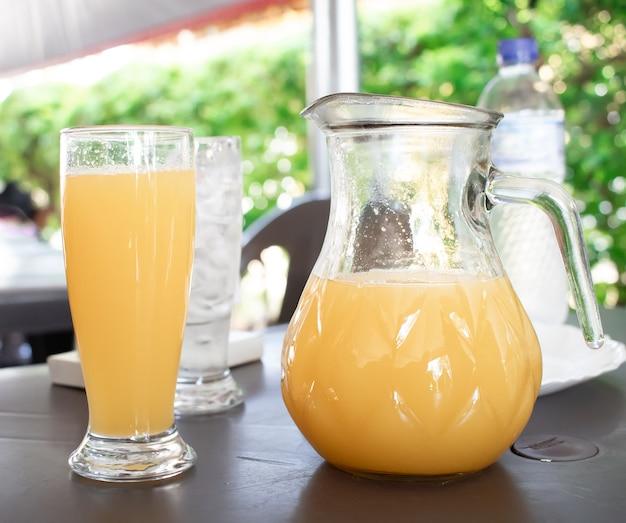 Un pot en verre de jus d'orange sur une petite table à l'extérieur à la lumière du jour