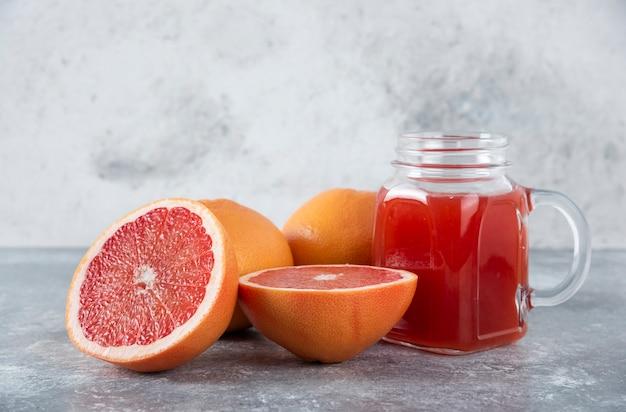 Pot en verre de jus de pamplemousse aigre frais avec des tranches de fruits.