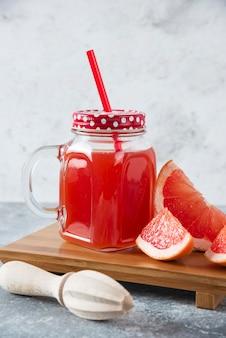 Pot en verre de jus de pamplemousse frais avec des tranches de fruits et un alésoir en bois.