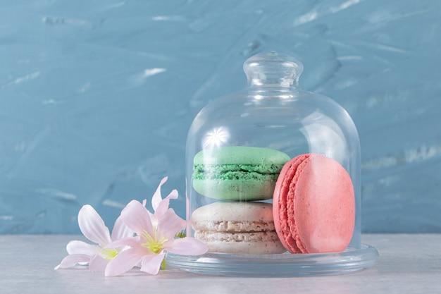 Pot en verre de macarons sucrés colorés sur fond de pierre.