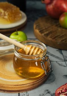 Pot en verre avec miel frais, cuillère à miel, pomme et grenade. concept nouvel an juif joyeuses fêtes roch hachana. disposition des symboles traditionnels. vue d'en-haut. shana tova