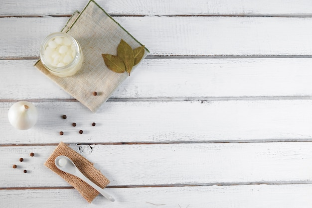 Pot de verre d'oignons marinés sur fond de bois blanc