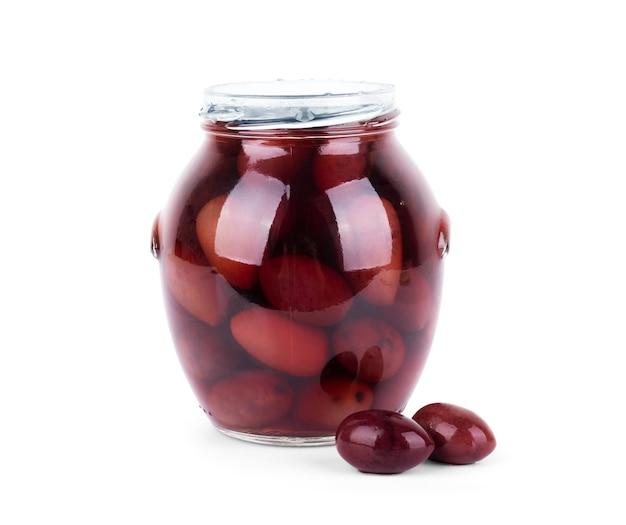 Pot en verre d'olives noires marinées isolé sur fond blanc