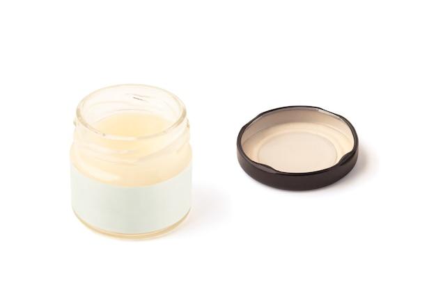 Pot en verre ouvert avec de l'huile cosmétique avec capuchon isolé sur une surface blanche
