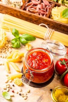 Pot en verre avec des pâtes aux tomates épicées ou une sauce à pizza classique faite maison.