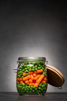 Pot en verre avec petits pois et carottes miniatures