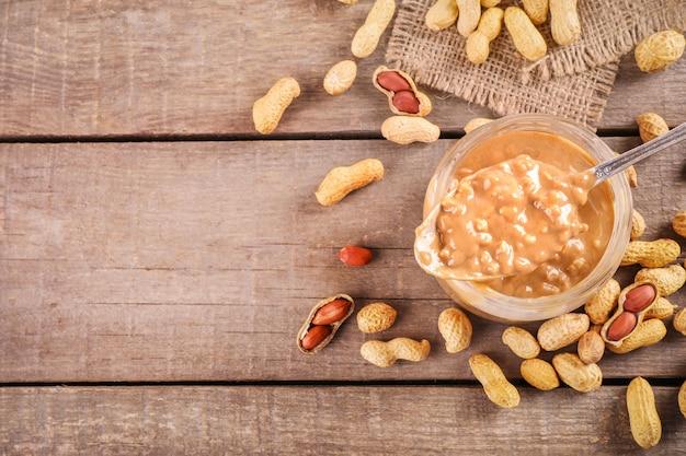 Pot en verre plein de beurre d'arachide croquant avec des arachides en bref à proximité sur bois