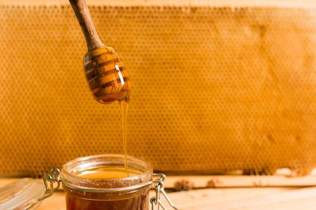 Pot en verre plein de miel avec une cuillère à miel
