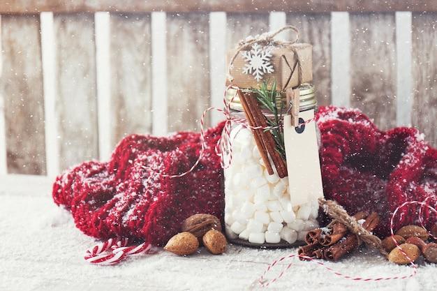 Pot en verre pleine de coton avec un cadeau sur le dessus