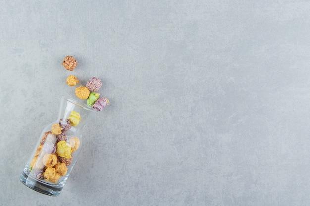 Un pot en verre de pop-corn multicolore sucré.