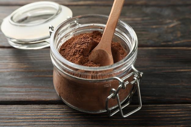 Pot en verre avec poudre de cacao et cuillère sur bois, gros plan