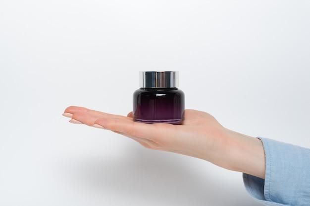 Pot en verre pour les cosmétiques dans une main féminine.