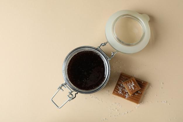 Pot en verre de sauce caramel et caramel salé sur fond beige