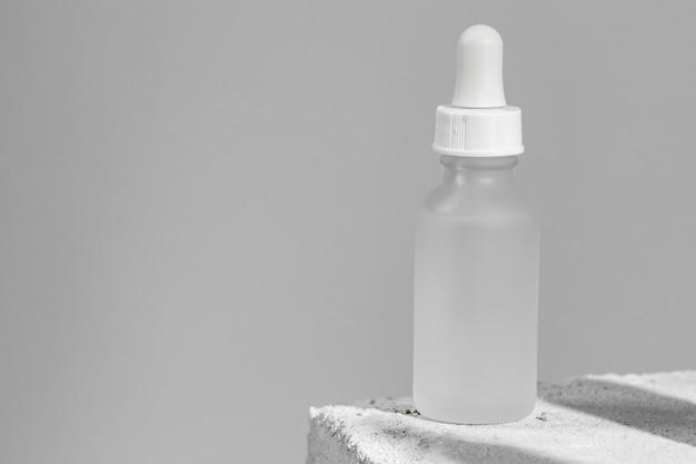 Pot en verre de sérum de soin de la peau sur bloc de béton