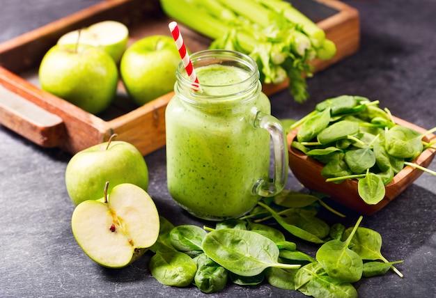 Pot en verre de smoothie de jus vert aux épinards, pomme et céleri sur noir