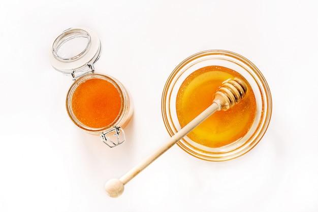 Pot en verre et soucoupe avec du miel et une cuillère pour le miel