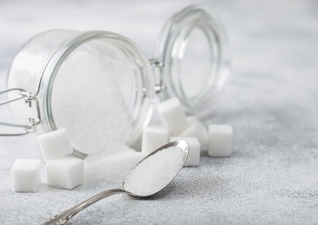 Pot en verre de sucre raffiné blanc naturel avec des cubes avec une cuillère en argent sur la lumière