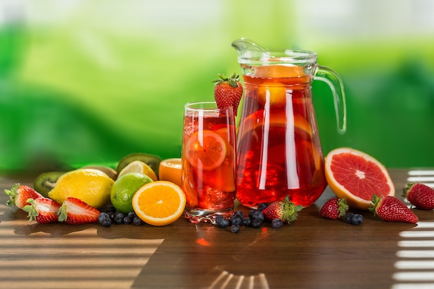 Pot et verre de thé aux agrumes sur table en bois