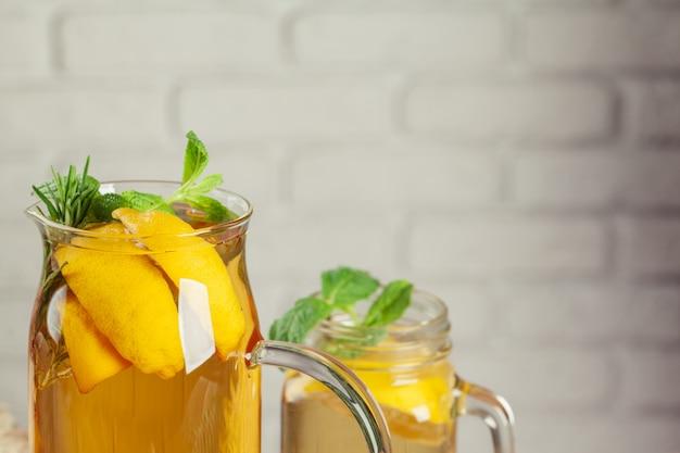 Pot en verre de thé vert ice au citron vert, citron, menthe sur une table en bois.