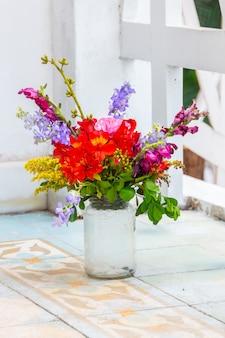 Pot en verre utilisé comme vase avec diverses fleurs à rio de janeiro.