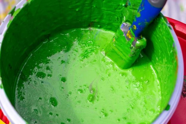 Un pot de vieille peinture verte avec un pinceau sale dedans. pot de peinture verte et pinceau. vue de dessus