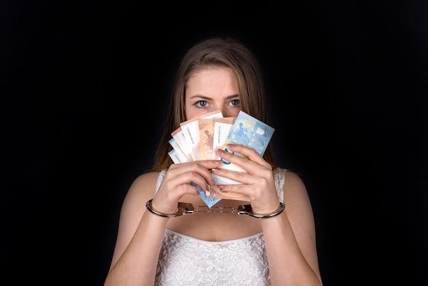 Pot-de-vin. femme menottes aux poignets montrant l'euro, isolé sur fond noir