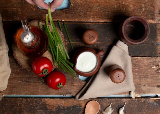 Un pot de yaourt, tomates, herbes et bouteille d'olive sur la table en bois