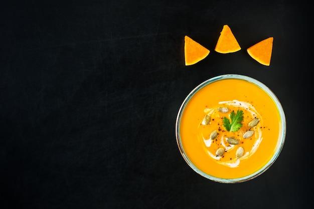 Potage à la citrouille et aux carottes avec crème, graines de citrouille et persil sur fond rayé noir.