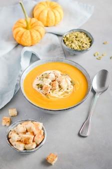 Potage à la citrouille avec crème, croûtons, graines de citrouille et thym sur béton gris ou pierre